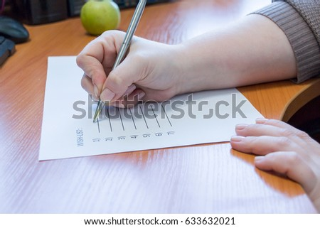 lose up of female hand writing her wish list with pen. business and happiness family concept. Wishes must come true #633632021