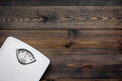 Lose weight concept. Scale on dark wooden background top view copyspace