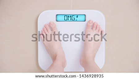 Lose weight concept with woman on a scale shows OMG