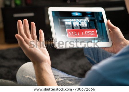 Losing money in online casino. Man playing online slot machine game with tablet. Gambling problem concept. Spreading hands. You lose text in app. Foto d'archivio ©
