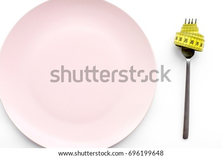 Losing weight. Strict diet. Empty plate and measuring tape on fork instead food on white background top view mockup