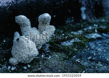Lost childhood concept. Dirty teddy bear lying down outdoors. Copy space for text or design. Horizontal image. ストックフォト ©