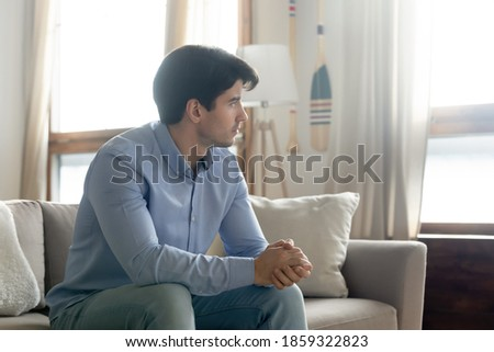 Lost in memories. Serious thoughtful millennial male sitting on couch at living room alone looking at distance thinking on problem, remembering past time events, preparing to make important decision Foto stock ©