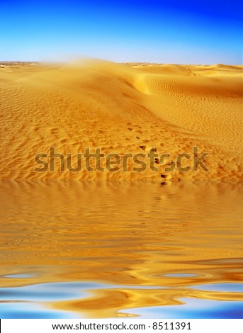 Lost in the Desert Mirage with footprints leading from water up into the Dunes  with sand blowing of the top.