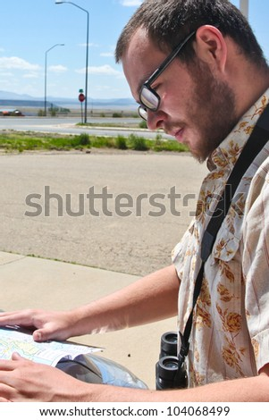Lost in the Southwestern US. Man in beard & glasses studies map by roadside with desolate background.