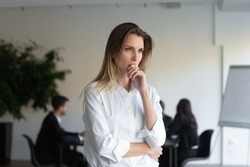 Lost in thoughts business lady entrepreneur standing in office feels concerned thinking of new challenges solving problems. Stressed woman applicant feels anxious about failed job interview concept