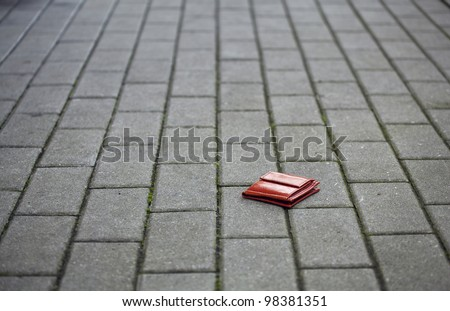 Lost leather wallet with money lost at sidewalk