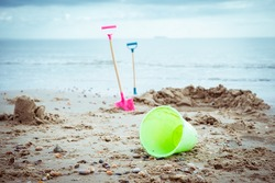 Lost, leaved children's beach toys - bucket, spade, and shovel on the sand on a cloudy day. No people. Devastation concept. Selective focus, copy space.