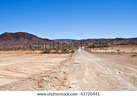 Lost outback unsealed road going through desert hills
