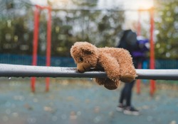Lost teddy bear doll lying on metal with rain drops at playground in gloomy day, Lonely or sad brown bear abandoned lied down alone in the park,Loneliness concept, International missing Children day