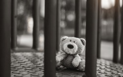 Lost teddy bear lying on metal bridge at playground in gloomy day, Lonely and sad face brown bear doll lied down alone in the park, lost toy or Loneliness concept, International missing Children day