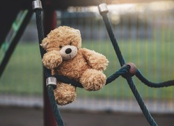 Lost teddy bear toy lying on rope frame at playground in gloomy day, Lonely and sad brown bear doll lied down alone in the park, lost toy or Loneliness concept, International missing Children day