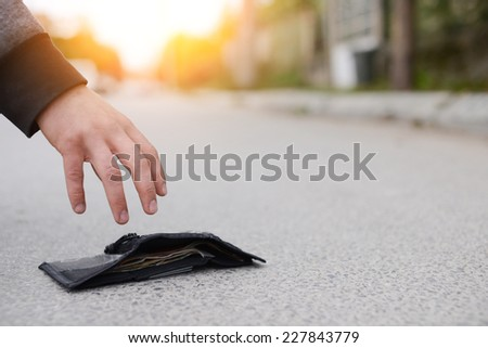 Lost wallet. Low section of man picking up fallen wallet on street.Lost black leather wallet with money lost at street