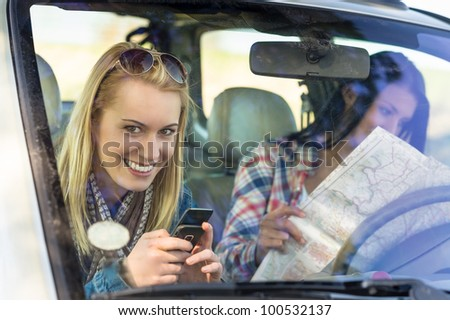 Lost with map two young friends in car enjoy road trip