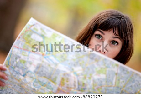 Lost woman in the countryside holding a map
