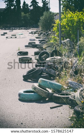 Lot of abandoned used tires in the resort area in the backyard vertical orientation (Rhodes, Greece) #1578625147