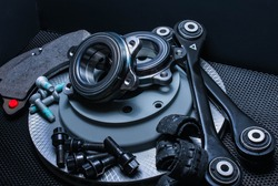 lot of car parts running gear: brake disc, pads and hub bearing with fasteners, isolated on a black background.