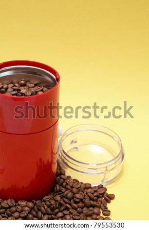 Lot of coffee beans near open modern red grinder on yellow background