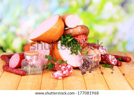 Lot of different sausages on wooden table on natural background