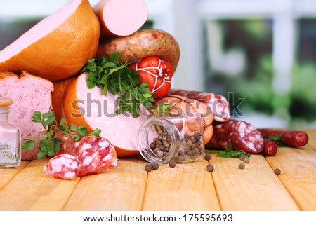 Lot of different sausages on wooden table on window background