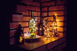 Lot of different vintage style beer bottles and green wine bottles decorated with wire string micro led lights on shelf, red brick wall background. Illuminated at night.