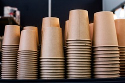 Lot of drinking paper coffee cups in piles. Stack of disposable coffee cup, selective focus