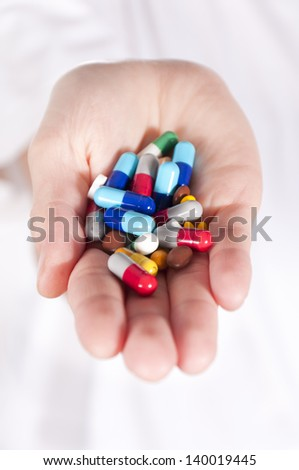 Lot of pills in hand. Selective focus on the pills in middle