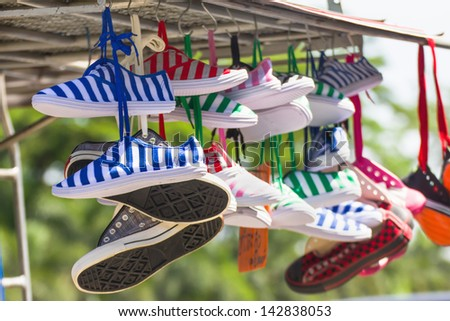 Lot of sneakers   shoes multicolored hanging on roof