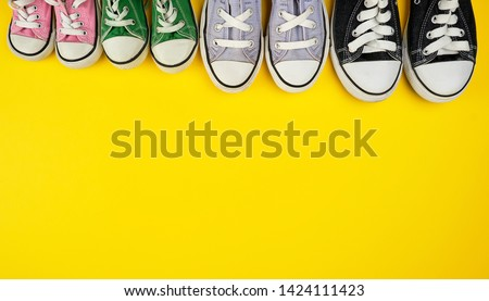 lot of textile worn sneakers of different sizes on a yellow background, empty space at the top, family concept