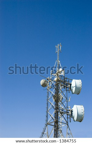 lot of transmission antennas mounted on a huge pylon over a deep blue sky