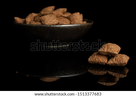 Lot of whole crispy brown cereal pillow in dark ceramic bowl isolated on black glass #1513377683