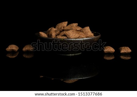 Lot of whole crispy brown cereal pillow in dark ceramic bowl isolated on black glass #1513377686