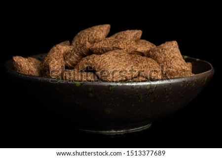 Lot of whole crispy brown cereal pillow in dark ceramic bowl isolated on black glass #1513377689
