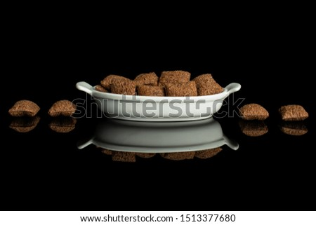 Lot of whole crispy brown cereal pillow in white oval ceramic bowl isolated on black glass #1513377680