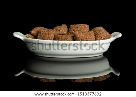 Lot of whole crispy brown cereal pillow in white oval ceramic bowl isolated on black glass #1513377692
