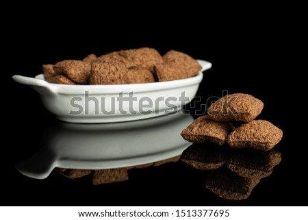 Lot of whole crispy brown cereal pillow in white oval ceramic bowl isolated on black glass #1513377695