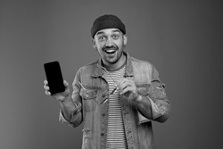 Lots of advantages. Excited handsome man having cheerful mood while presenting his modern smartphone and being full of happiness