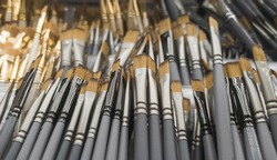 Lots of art brushes on the counter for sale. Showcase with brushes.