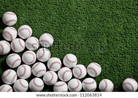 Lots of baseballs on green turf background