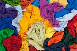 Lots of bright messy colorful clothing, abstract background.