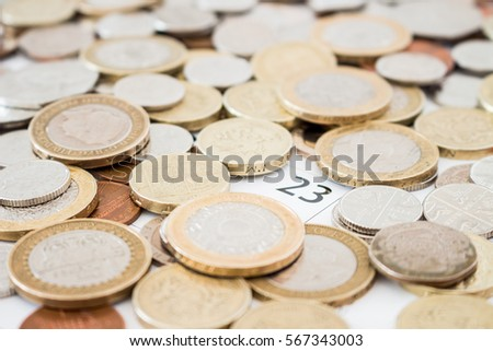 Lots of British, metal money, various coins, lots of coins, on a calendar around the 23rd day.