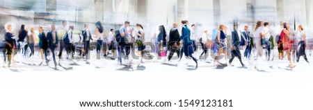 Lots of business people walking in the City of London. Blurred image, wide panoramic view of the road with people at sunny day. London, UK