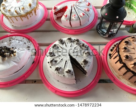 Lots Of Cakes On Pink Cake Tray On White Table Various Color Various Design Variety Flavors Chocolate, Red Velvet, Cream And Cookies