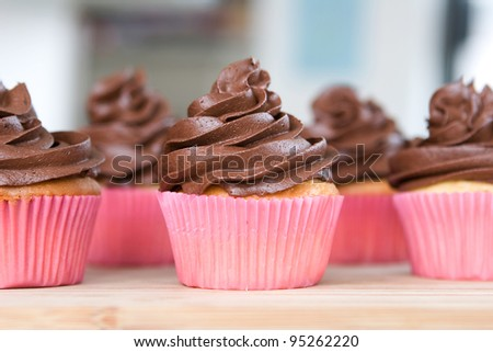 Lots Of Chocolate Frosted Cupcakes In Pink Wrappers Stock Photo ...