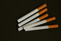 Lots of cigarettes on black background. The concept of World No Tobacco, Tobacco and Lung Health. Copy space. Harm to health. It is bad habit. View from above. Cigarettes with yellow filter are whole.