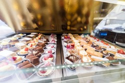 Lots of colorful and tasteful cakes in a patisserie shop