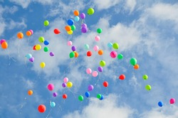 Lots of colorful balloons flying against blue sky with clouds with copy space. Concept of holiday, Children's Day, Last call at school and kindergarten, birthday.