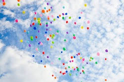 Lots of colorful balloons flying against blue sky with clouds with copy space. Concept of holiday, Children Day, Last call at school and kindergarten, birthday.