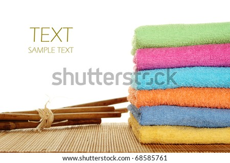 Lots of colorful bath towels stacked on each other. Side by side on a wooden surface lie bamboo sticks. Isolated