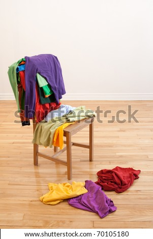 Lots of colorful messy clothes on a chair and on a wooden floor.